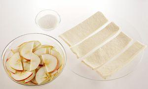 Тесто разморозьте, нарежьте полосками, шириной примерно 3-4см. Яблоки промойте, нарежьте тонкими полукольцами, залейте водой и поставьте в микроволновую печь на 1-2 минуты ( в зависимости от мощности Вашего оборудования), чтобы они были немного мягкими и не ломались в процессе приготовления.