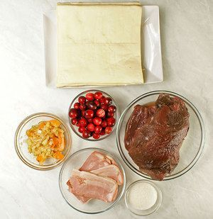 Мясо оленя разморозить естественным способом на нижней полке холодильника. Зачистить от пленок и сухожилий. Выбрать крупные кусочки, убрать в холодильник на сутки, замариновав в смеси уксуса и воды. Лук и морковь нарезать крупно, обжарить на разогретой с оливковым маслом сковороде.