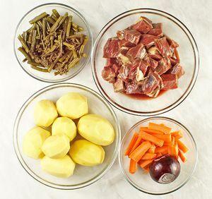Мясо жеребенка разморозить естественным способом на нижней полке холодильника. Нарезать крупными кубиками, замариновать в смеси специй и оливковом масле на 30-40 минут. Папоротник вымочить в горячей воде в течение 12 часов, периодически меняя воду. Овощи (картофель, лук, морковь) почистить.