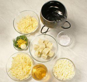 Сыр натереть на терке, с багета срезать корочку и нарезать произвольными кубиками. Чеснок натереть на терке, цедру лимона нарезать тонкой соломкой