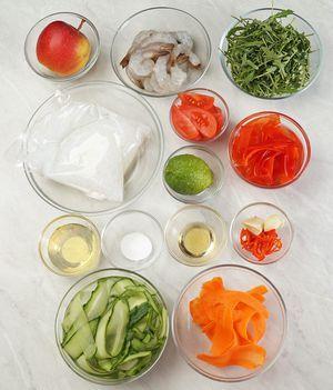 Огурцы свежие  и красный перец нарезать тонкими пластиками с помощью овощечистки, положить в холодную воду.  Креветки разморозить естественным образом на нижней полке холодильника, с помощью зубочистки удалить кишечную вену, снять панцирь, оставляя хвостики.