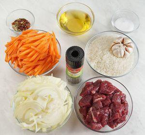 Морковь нарезать толстой, длинной соломкой толщиной 0,5х0,5см, лук нарезать полукольцом. Говядину нарезать крупным кубиком. Чеснок промойте, не очищайте.