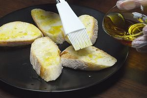 Багет нарезать на порции, под углом, толщиной примерно 1-1,5см. Смазать оливковым маслом.
