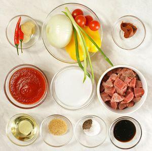 Мясо разморозьте естественным способом на нижней полке холодильника, нарежьте небольшими кубиками, лук и чеснок почистите. У перца чили и желтого перца удалите семена.