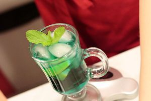 В бокал для коктейля влить сироп Блю Курасао и сироп Мята, добавить 1-2 дольки лайма.