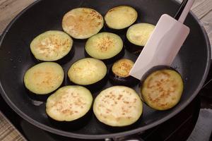 Баклажаны обжарить с двух сторон на хорошо разогретой сковороде с растительным маслом до золотистого цвета.