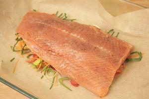 В центр бумаги для запекания (размер пергамента должен быть больше филе,чтобы можно было завернуть внахлест) выложить 1/2 часть сливочного масла, затем смесь из нарезанных овощей. На овощи - филе подготовленной рыбы.