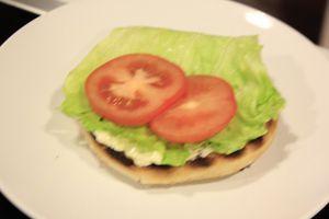 На украшенную тарелку выложить булочку, смазать майонезом и соусом барбекю, положить лист салата, хрустящий лучок, затем помидор, котлету.