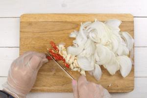 Лук репчатый нарезать полукольцами, чеснок раздавить ножом и порубить. Перец нарезать кольцами (чтобы снизить остроту, удалить семенную коробку и перегородки).