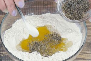 В глубокой чашке смешайте муку, воду, масло и сушеные травы.