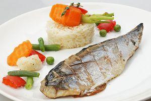 На тарелку, с помощью кулинарного кольца, выложить башенкой рис, затем украсить бланшированными овощами. Рядом выложить филе скумбрии.