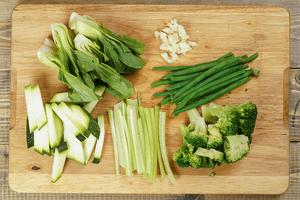 Нарезать сельдерей соломкой, кабачки брусочком, брокколи разрезать на соцветия, салат пак чой поделить на 2-3 части, чеснок мелко порубить.