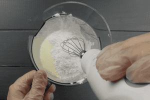 В глубокой чаше взбить сливки с сахарной пудрой до плотной массы