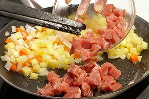 На разогретой с растительным маслом сковороде обжарьте сначала лук и морковь до золотистого цвета, затем добавьте картофель, жарьте еще 2-3 минуты. Отодвиньте овощи в сторону и обжарьте на второй половине сковороды мясо.