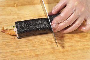 Нож смочите в воде и разрежьте ролл пополам.