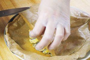 Готовую рыбу переложить на тарелку, снять пергамент, украсить лимоном, зеленью, посолить, поперчить по вкусу.