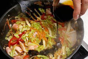 Добавить красный перец соломкой, обжарить 2-3 минуты. В конце приготовления добавить китайскую капусту, обжаренный кальмар и влить соус терияки. Перемешивать 1-2 минуты, снять с огня.