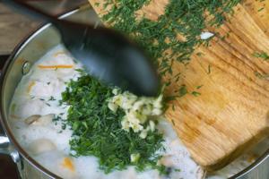 Зелень и чеснок мелко порубить. Суп снять с огня и добавить зелень.