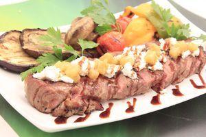 Мясо нарежьте пластиками, выложите на тарелку, украсьте сыром рикота и чатни из груши. Рядом положите овощи-гриль, зелень, полейте соевым топингом.