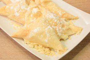 На смазанный сливочным маслом противень выложить готовые треугольнички, выпекать в разогретой до 180С духовке 10-15 минут, до золотистого цвета.