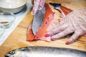 Тушку рыбы разделать на чистое филе с кожей: отрезать голову, затем разрезать вдоль хребта на 2 части. Срезать брюшные косточки.
