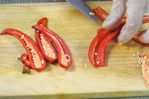 Перец красный острый разрезать пополам, очистить от семян и перегородок.