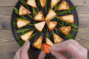 Клубнику наколоть на шпажки или зубочистки, украсить сыр сверху.