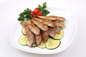 Маринованные кабачки выложить в один слой на тарелку, сверху выложить обжаренную рыбу, украсить зеленью и мини-помидорками.
