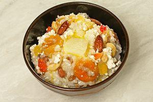 Переложить готовую кашу в тарелку, в центр выложить творог,  украсить орешками, цукатами и кусочком сливочного масла