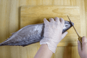 Хорошо замороженную рыбу промыть под холодной водой, обсушить бумажным полотенцем. Отрезать острую часть головы (для того, чтобы удобнее было строгать филе и рыба не скользила по доске).