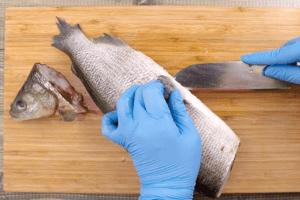 Рыбу разморозить естественным способом на нижней полке холодильника, очистить от чешуи. Сделать разрез вдоль брюшка, удалить внутренности, голову и хвост.