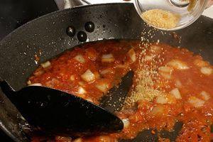 К луку добавьте красную пасту карри по вкусу и коричневый сахар, обжаривайте еще 2-3 минуты