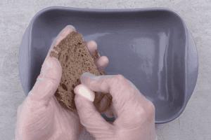 Хлеб нарезать пластиками толщиной 1-1,5см, натереть чесноком или выложить раздавленный чеснок сверху. Поставить в духовку подсушиться минут на 10-15 при температуре 150-160С.
