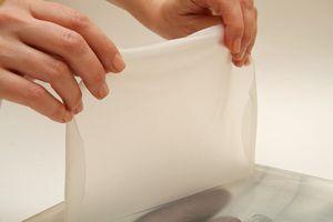 Бамбуковый коврик макису завернуть в пищевую плёнку. Подготовить широкую миску с водой.