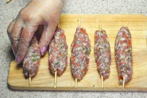 Разделить на порционные колобки, приминая рукой слепить колбаску вокруг деревянных шпажек.