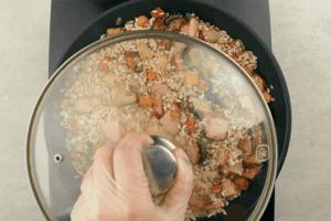 Влить воду, добавить соль и специи. Накрыть крышкой и потушить на слабом огне примерно 40 минут. Рис должен распариться, но не перевариться.