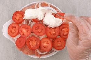 На лук уложить помидоры, смазать слоем сметаны. Поставить в разогретую до 190С духовку на 15-20 минут