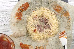 Пока масло плавится, сверху выложить лаваш, смазать кетчупом, добавить ветчину, сыр.