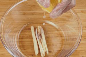 В чашку выложить палочки лемонграсса, выдавить лимонный сок.