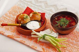 Подайте борщ со сметаной, зеленым луком, салом и чесночными пампушками.