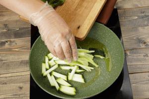 На разогретой с растительным маслом сковороде обжарить слегка цуккини и сельдерей.