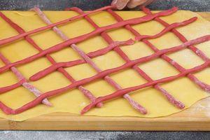 Затем тонко раскатываем основное тесто, прямоугольником, выкладываем рисунок из розовых жгутиков в виде сеточки.