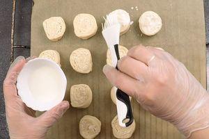 Переложить булочки разрезом вверх на пергамент, смазать кефиром (можно взять сметану).
