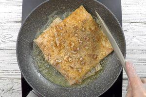 Завернуть лаваш в виде конверта, перевернуть на другую сторону, увеличив огонь, обжарить до золотистого цвета, чтобы сыр расплавился, а белок схватился.