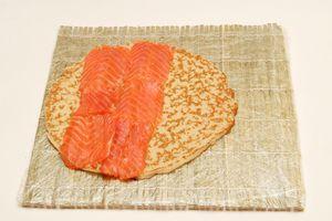 Нарезать слабосолёную сёмгу тонкими пластами и выложить рыбу сплошным слоем примерно на половину блина