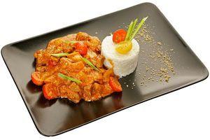 С помощью кулинарного кольца выложите на тарелку жасминовый рис с кокосовым молоком. Рядом выложите красное карри. По желанию украсьте зеленью и помидорками черри