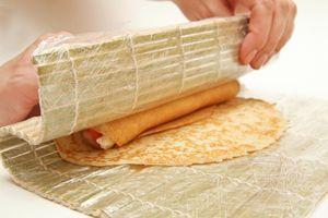 С помощью коврика свернуть блин рулетом, лёгким давлением пальцев распределить начинку равномерно