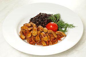 Выложить на тарелку горкой готовый рис рядом тушеные с овощами язычки, украсить свежей зеленью и долькой помидора