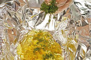 В форму для запекания выстелить фольгу, в центр фольги положить несколько ложек меда, тертый имбирь, зелень