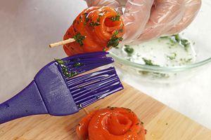 Пока суп готовится, из филе рыбы нарезать полоски, толщиной 2-3мм, свернуть рулетиками, скрепить с одной стороны зубочисткой. Смазать растительным маслом.